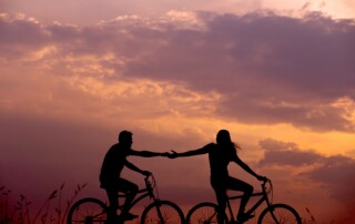 healthy active couple riding bikes in the sunset